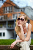 Woman waiting in front of house. Young woman with sunglasses waiting in front of a house Royalty Free Stock Images