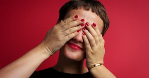 Woman waiting a gift with a n eyes closed with two hands. On red background stock video footage