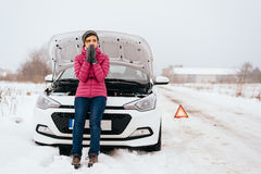 Woman waiting for help or assistance - winter car breakdown. Young woman waiting for help or assistance after her car breakdown in the winter. Broken down car royalty free stock photo