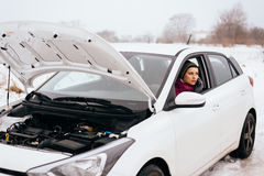 Woman waiting for help or assistance - winter car breakdown. Young woman waiting for help or assistance after her car breakdown in the winter. Broken down car Royalty Free Stock Photos