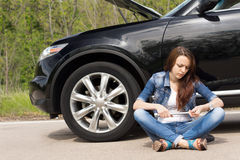 Woman waiting beside her broken down car. Sitting crossed legged on the road fiddling with the wheel spanner as she waits for roadside assistance Stock Photography