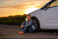Woman waiting beside her car on a rural road Stock Photos