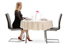 Woman waiting for her date. Studio shot of a young woman sitting alone at a restaurant table and waiting for her date isolated on white background Stock Photography