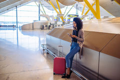 Woman waiting her flight using mobile phone at the airport royalty free stock image