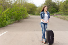 Woman waiting with her suitcase in the road stock photo