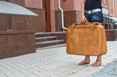 Woman waiting with her suitcase in the street royalty free stock image