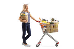 Woman waiting in line with shopping cart and paper bag. Full length profile shot a young woman waiting in line with a shopping cart and a paper bag isolated on Royalty Free Stock Images