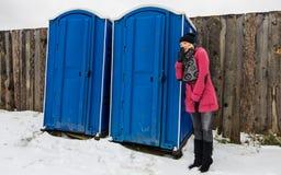 Woman waiting outside toilette Stock Photo