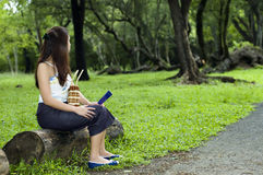 Woman waiting at park. Part of series. Woman waiting for someone to arrive. She is holding a fan Stock Image