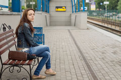 Woman waiting at a railway station for transport Stock Photos
