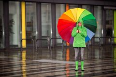Woman waiting in the rain with her rain cloth Royalty Free Stock Photo