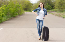Woman waiting in the road with her suitcase Stock Photos