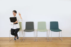 Woman in waiting room poiting finger up, idea Stock Images