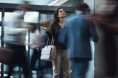 Woman waiting during rush hour in lobby. Businesswoman standing and looking upwards while waiting for someone with people rushing in the lobby. Motion blur stock images