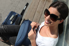 Woman waiting with a suitcase. Woman in sunglasses waiting with a suitcase Royalty Free Stock Photography