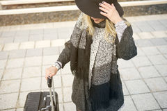 Woman waiting with suitcase at train station Royalty Free Stock Photography