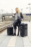 Woman waiting with suitcases at train station. Blond woman waiting at train station with her suitcases looking at her watch Royalty Free Stock Photography