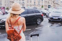 Woman waiting for taxi, tourist commuter. With suitcase and backpack royalty free stock images