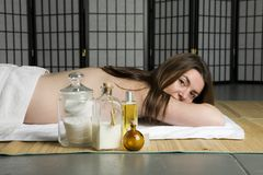 Woman waiting to be pampered. Lying on a spa mat with products in the foreground Royalty Free Stock Photography
