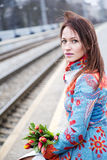Woman waiting train with flowers at hand Stock Photo