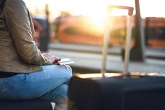 Woman waiting for train with passport, ticket and suitcase. Lady with baggage in station at sunset. Travel, vacation and transportation concept Royalty Free Stock Images
