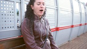 Woman is waiting for train on platform and yawns stock footage