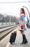 Woman waiting train with suitcase and flowers Stock Image