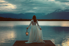 Woman Waiting With Lantern On A Pier Royalty Free Stock Images