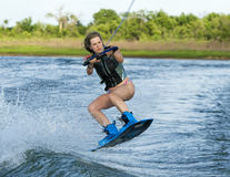 Woman wakeboarding. A physically fit beautiful woman is jumping the wake on her wakeboard. She is concentrating intensely on the landing. The location is royalty free stock image