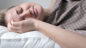 Woman wakes up in bed stock video footage