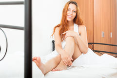 Woman wakes up in  bed Royalty Free Stock Image