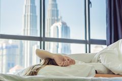 Woman wakes up in the morning in an apartment in the downtown area with a view of the skyscrapers. Life in the noise of. The big city concept. Not enough sleep stock photo