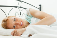 Woman waking in her bed Stock Photos