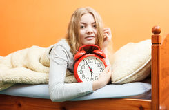 Woman waking up with alarm clock in morning Royalty Free Stock Photos