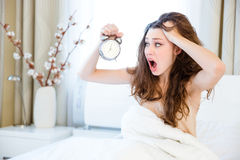Woman waking up with alarm Royalty Free Stock Images