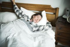 A woman waking up in bed Stock Images