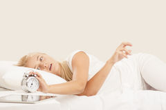 Woman waking up in bed. Blonde woman waking up in bed stock photography