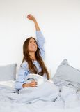 Woman waking up in bed with cup of coffee Stock Photography