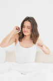 Woman waking up in bed with eyes closed Royalty Free Stock Photos