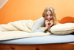 Woman waking up in bed in morning after sleeping Stock Photography
