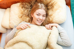 Woman waking up in bed in morning after sleeping Stock Image