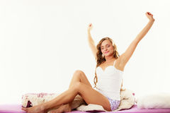 Woman waking up in bed stretching her arms up Royalty Free Stock Photos