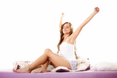 Woman waking up in bed and stretching her arms up Stock Photo