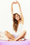 Woman waking up in bed stretching her arms up Royalty Free Stock Images