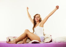 Woman waking up in bed stretching her arms up Royalty Free Stock Image