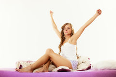 Woman waking up in bed stretching her arms up Stock Photos