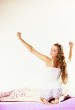 Woman waking up in bed stretching her arms up Stock Image