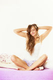 Woman waking up in bed stretching her arms up Royalty Free Stock Photo