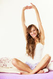 Woman waking up in bed stretching her arms up Stock Photography