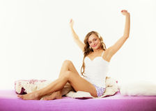 Woman waking up in bed stretching her arms up Stock Photo